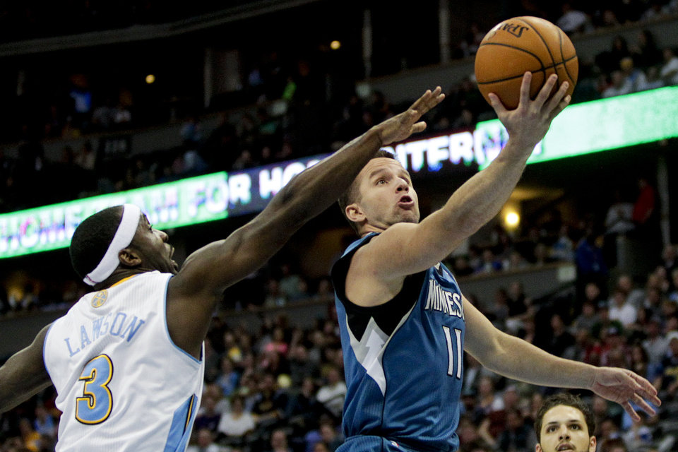 Photo - Minnesota Timberwolves'  J.J. Barea (11) makes a layup past Denver Nuggets' Ty Lawson (3) during the third quarter of an NBA basketball game Monday, March 3, 2014, in Denver. The Timberwolves won 132-128. (AP Photo/Barry Gutierrez)