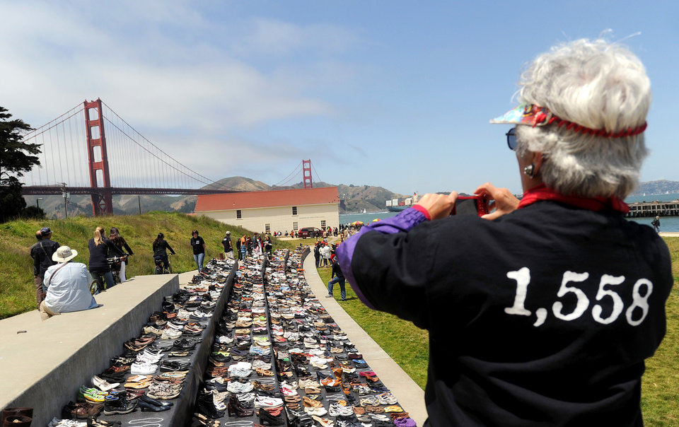 Photo -   Roberta McLauglin photographs an exhibit of shoes in remembrance of people who have jumped from the Golden Gate Bridge during a commemoration of the bridge's 75th anniversary on Sunday, May 27, 2012, in San Francisco. The Bridge Rail Foundation, which advocates for a safety net along the span to prevent suicides, estimates approximately 1,558 people have died after jumping since the bridge opened. (AP Photo/Noah Berger)