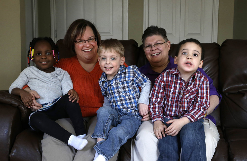 Photo - FILE - In this March 5, 2013, file photo, April DeBoer, second from left, sits with her adopted daughter Ryanne, 3, left, and Jayne Rowse, fourth from left, and her adopted sons Jacob, 3, middle, and Nolan, 4, right, at their home in Hazel Park, Mich. A federal judge has struck down Michigan's ban on gay marriage, Friday, March 21, 2014, the latest in a series of decisions overturning similar laws across the U.S. The two nurses who've been partners for eight years claimed the ban violated their rights under the U.S. Constitution. (AP Photo/Paul Sancya, File)