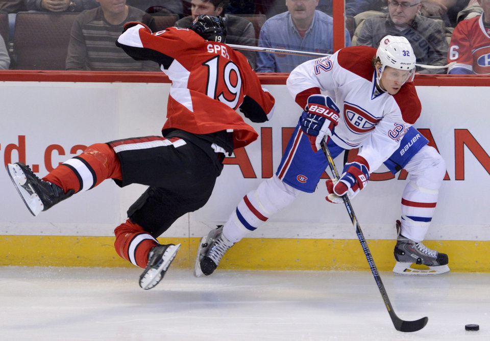 Photo - Montreal Canadiens left wing Travis Moen handles the puck as Ottawa Senators center Jason Spezza crashes into the boards during the first period of an NHL hockey game Thursday, Jan. 16, 2014, in Ottawa, Ontario. (AP Photo/The Canadian Press, Adrian Wyld)