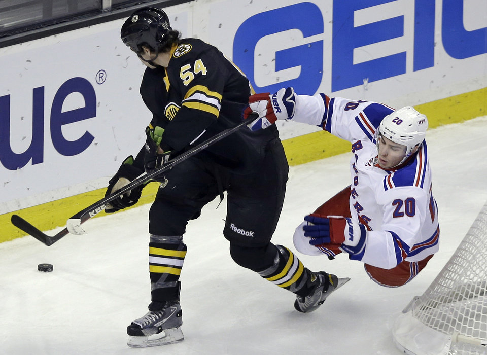 New York Rangers left wing Chris Kreider (20) goes airborne as he chases the puck against Boston Bruins defenseman Adam McQuaid (54) during the first period of an NHL hockey game in Boston, Tuesday, Feb. 12, 2013. (AP Photo/Elise Amendola)