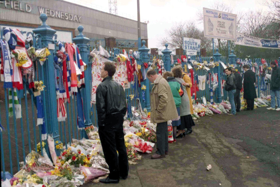 Photo - FILE- In this file photo dated April 17, 1989, soccer fans arrive to pay their respects and look at the flowers, scarves and banners, left on the gates at Hillsborough Football Stadium, after the Hillsborough April 15 tragedy when fans surged forward during the Cup semi-final between Liverpool and Nottingham Forest at Hillsborough Stadium killing 96 people. After years of campaigning to expose alleged wrongdoing by the authorities, new inquests into Britain's worst sports disaster are beginning Monday March 31, 2014, with the families of the 96 Liverpool fans crushed to death at Hillsborough seeking verdicts of unlawful killing. (AP Photo/ Peter Kemp, FILE)