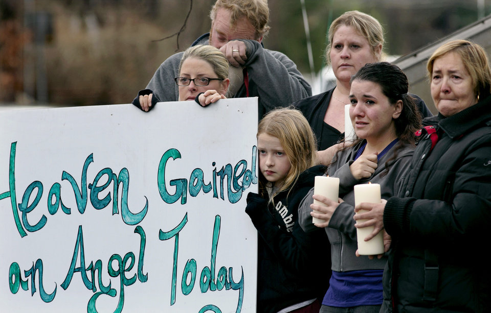 Photo - Tom Doyle, back left, standing with family and co-workers, wipes his face as the funeral procession for 6-year-old James Mattioli, who died in the Sandy Hook Elementary School shootings, approaches the St. John's Cemetery Tuesday, Dec. 18, 2012, in Darien, Conn. Center are his wife Debbie and daughter Emily, 10. Adam Lanza opened fire at the Sandy Hook Elementary School in Newtown on Friday, killing 26 people, including 20 children. (AP Photo/Craig Ruttle)