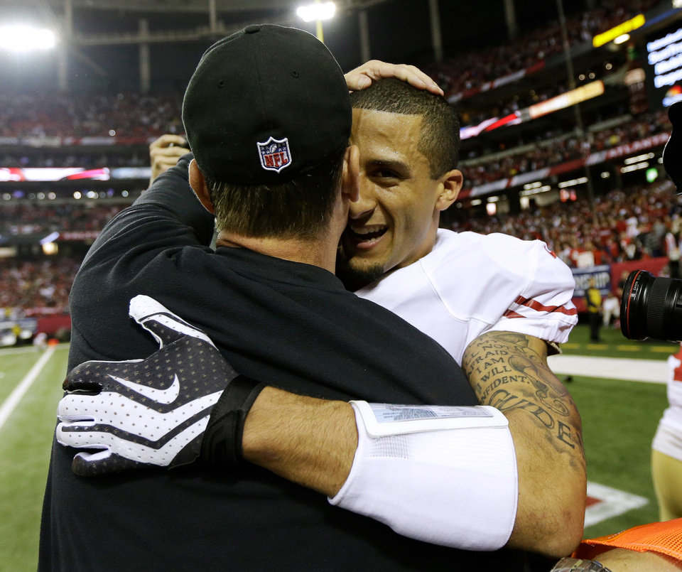 San Francisco 49ers head coach Jim Harbaugh, left, hugs Colin Kaepernick after the NFL football NFC Championship game against the Atlanta Falcons Sunday, Jan. 20, 2013, in Atlanta. The 49ers won 28-24 to advance to Superbowl XLVII. (AP Photo/Mark Humphrey)