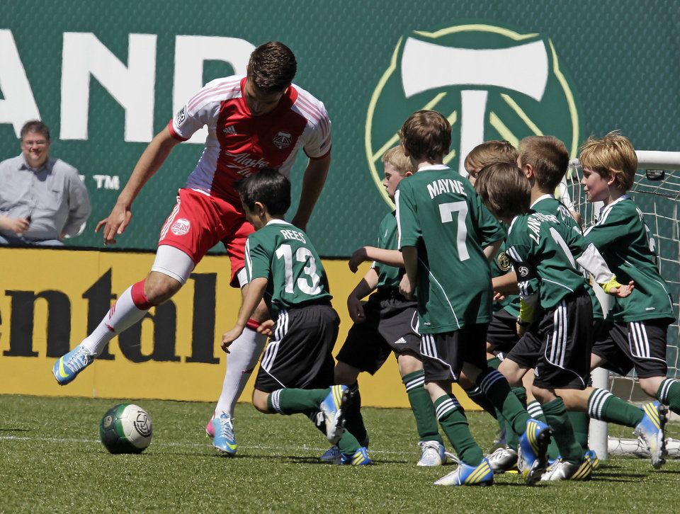 Portland Timbers defender Ryan Kawulok, left, is mobbed by members of the Green Machine soccer team as they play in Portland, Ore., Wednesday, May 1, 2013. The Timbers and Make-A-Wish Oregon treated the Green Machine and one of their players, Atticus Lane-Dupre, to a game at Jeld-Wen Field with more than 3,000 fans coming out to lend their support. Atticus missed the Green Machine's final match last fall because of cancer treatment. (AP Photo/Don Ryan)