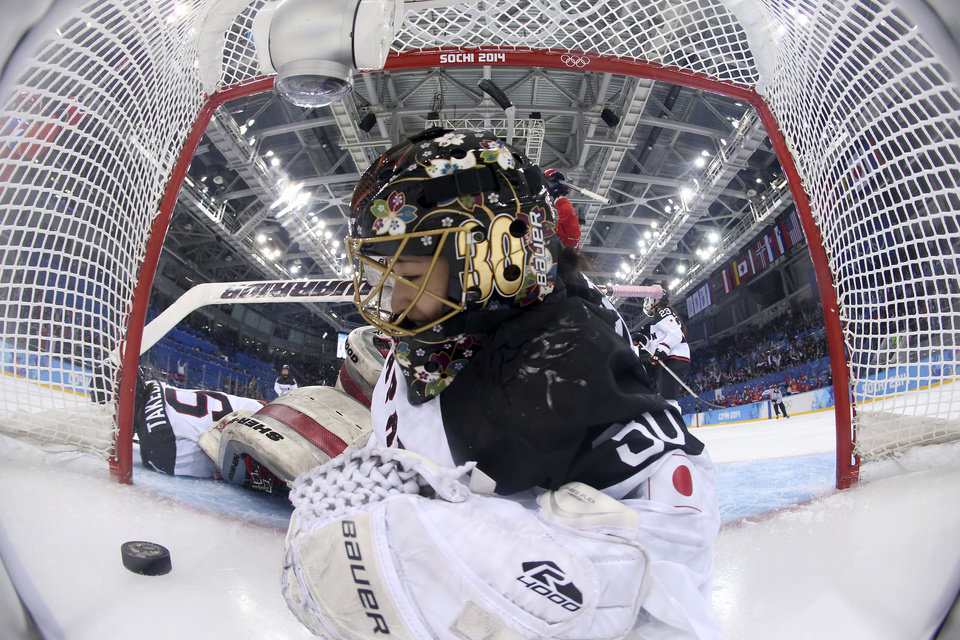 Photo - Goalkeeper Nana Fujimoto of Japan looks at the puck after sliding in after it on a score by Galina Skiba of Russia during the 2014 Winter Olympics women's ice hockey game at Shayba Arena, Sunday, Feb. 16, 2014, in Sochi, Russia. Russia defeated Japan 6-3. (AP Photo/Martin Rose, Pool)