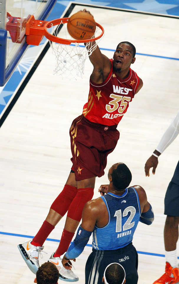 Western Conference's Kevin Durant (35), of the Oklahoma City Thunder, dunks over Eastern Conference's Dwight Howard (12), of the Orlando Magic, during the first half of the NBA All-Star basketball game, Sunday, Feb. 26, 2012, in Orlando, Fla. (AP Photo/Lynne Sladky)