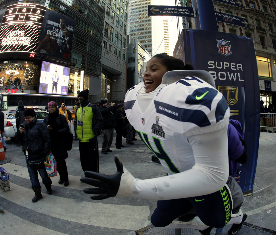 Photo - Adenike Forde, age 7, has her photo taken on a body of a Seattle Seahawks football player during Super Bowl Boulevard activities Wednesday, Jan. 29, 2014, in New York. The Seattle Seahawks are scheduled to play the Denver Broncos in the NFL Super Bowl XLVIII football game on Sunday, Feb. 2, in East Rutherford, N.J. (AP Photo/Charlie Riedel)