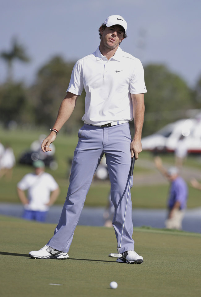 Photo - Rory McIlroy of Northern Ireland reacts after his ball misses the ninth hole during the first round of the Cadillac Championship golf tournament Friday, March 7, 2014, in Doral, Fla.  A severe thunderstorm delayed play on Thursday. (AP Photo/Lynne Sladky)
