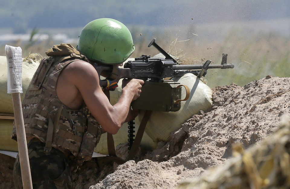 Photo - A Ukrainian soldier shoots with a machine gun during a battle with pro-Russian separatist fighters at Slovyansk, Ukraine, Friday, June 6, 2014. At least five Ukrainian soldiers were wounded, two of them heavily in this short clash with the pro-Russian separatist fighters. Ukraine's president elect and Russian President Vladimir Putin met Friday on the sidelines of D-Day commemorations in their first meeting since the start of the Ukrainian crisis, which touched on key issues, a French official said.  (AP Photo/Efrem Lukatsky)