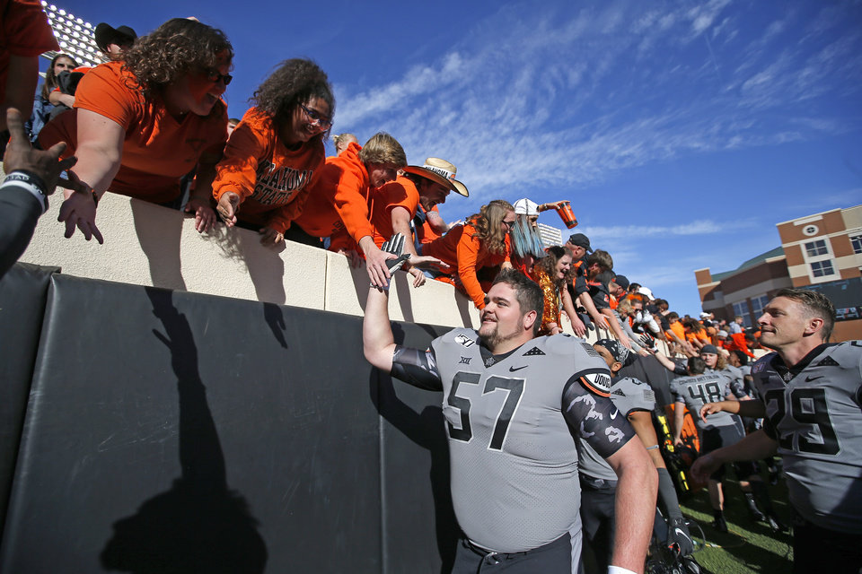 Photo - Oklahoma State's Walker Reed (57) celebrates with fans following the college football game between the Oklahoma State University Cowboys and the Kansas Jayhawks at Boone Pickens Stadium in Stillwater, Okla., Saturday, Nov. 16, 2019. OSU won 31-13. [Sarah Phipps/The Oklahoman]
