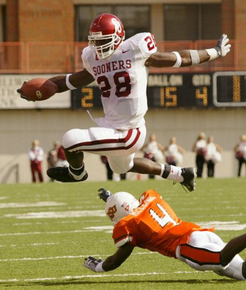 OU's Adrian Peterson leaps over OSU's Daniel McLemore during the University of Oklahoma at Oklahoma State University Bedlam college football at Boone Pickens Stadium in Stillwater, Okla., October 30, 2004.  By Doug Hoke, The Oklahoman