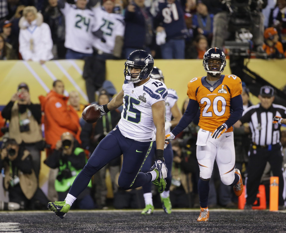 Photo - Seattle Seahawks' Jermaine Kearse (15) scores on a 23-yard touchdown reception in front of Denver Broncos' Mike Adams (20) during the second half of the NFL Super Bowl XLVIII football game Sunday, Feb. 2, 2014, in East Rutherford, N.J. (AP Photo/Matt Slocum)