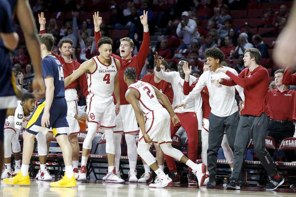 Photo - Oklahoma's Aaron Calixte (2) celebrates with Jamuni McNeace (4) and others on the Oklahoma bench after making a basket during an NCAA college basketball game between the University of Oklahoma (OU) and West Virginia at Lloyd Noble Arena in Norman, Okla.,  Saturday, March 2, 2019. Oklahoma won 92-80. Photo by Bryan Terry, The Oklahoman