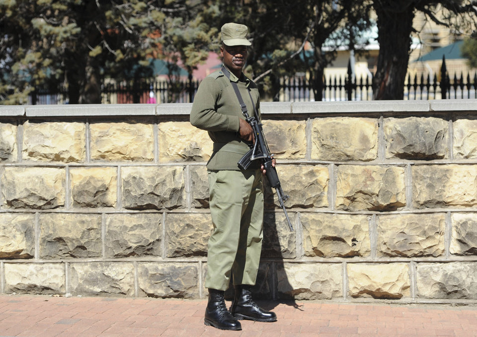 Photo - In THIS , Sunday Aug. 31, 2014 photo, an armed soldier stands outside the military headquarters in Maseru, Lesotho. Lesotho's prime minister fled to South Africa in fear for his safety and will now meet with leaders of the region there to seek peace, he said Sunday. Prime Minister Thomas Thabane said there had been an attempt to take over Lesotho, a country of about 2 million people that is surrounded by South Africa. Lesotho's Defense Forces deny any attempt at a coup although they say the military exchanged gunfire and disarmed two police stations in Lesotho's capital, Maseru, on Saturday.  (AP Photo)