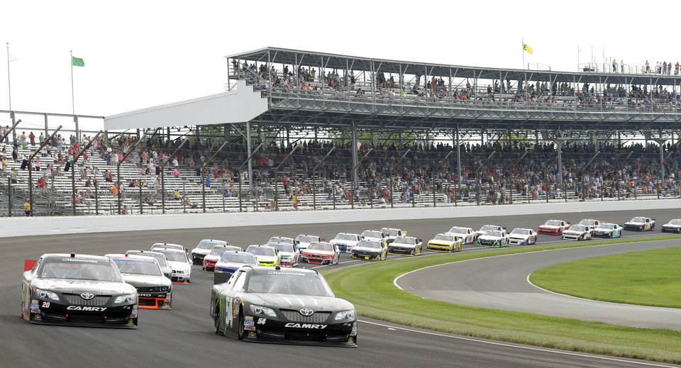 Photo - Kyle Busch (54) leads the field out of Turn1 following the start of the Nationwide auto race at Indianapolis Motor Speedway in Indianapolis, Saturday, July 26, 2014. (AP Photo/Darron Cummings)