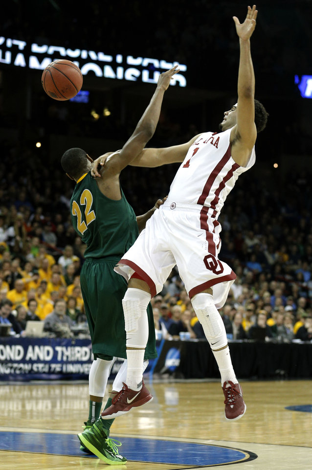 Oklahoma's Frank Booker (1) ooosed the ball as North Dakota State's Lawrence Alexander (12) defends during the NCAA men's basketball tournament game between the University of Oklahoma and North Dakota State at the Spokane Arena in Spokane, Wash., Thursday, March 20, 2014. Oklahoma home lost 80-75. Photo by Sarah Phipps, The Oklahoman