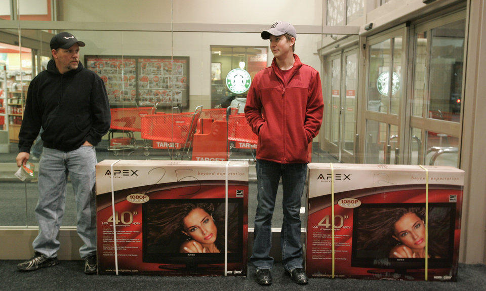 Photo - David Hollifield of Norman and Tom Davis of Arkansas wait at the front of Norman's Super Target with their TVs during after Thanksgiving shopping Fri. Nov. 27, 2009. Photo by Jaconna Aguirre, The Oklahoman.
