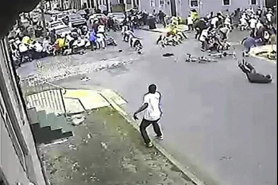 Photo - In this image taken from video and provided Monday, May 13, 2013, by the New Orleans Police Department, a possible shooting suspect in a white shirt, bottom center, shoots into a crowd of people, Sunday in New Orleans. Police believe more than one gun was fired in the Mother's Day gunfire that wounded 19 people during a New Orleans neighborhood parade. (AP Photo/New Orleans Police Department)