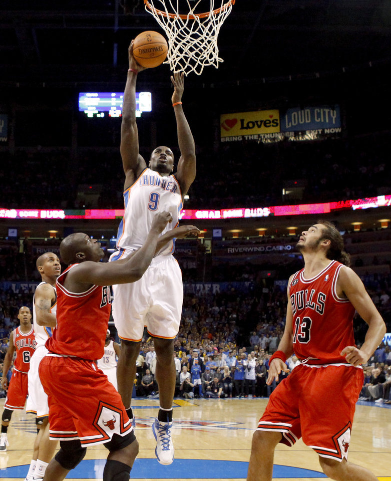 Photo - Oklahoma City's Serge Ibaka goes to the basket between Chicago's Luol Deng, left, and Joakim Noah during the NBA basketball game between the Oklahoma City Thunder and the Chicago Bulls in the Oklahoma City Arena on Wednesday, Oct. 27, 2010. Photo by Bryan Terry, The Oklahoman