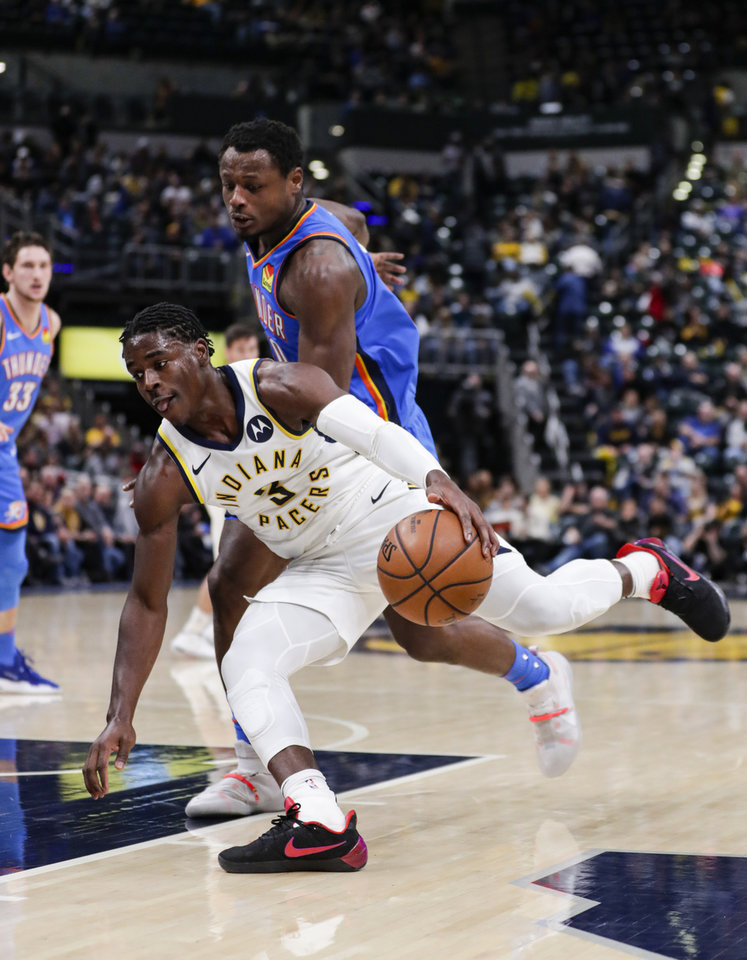 Photo - Indiana Pacers guard Aaron Holiday (3) cuts around Oklahoma City Thunder's Deonte Burton during the second half of an NBA basketball game in Indianapolis, Tuesday, Nov. 12, 2019. The Pacers defeated the Thunder 111-85. (AP Photo/Michael Conroy)