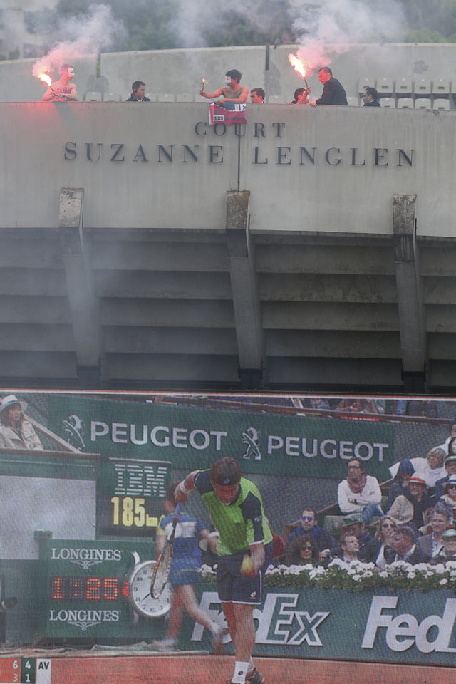 Photo - Security officiers remove demonstrators display a banner demanding the resignation of French President  Francois Hollande, atop Suzanne Lenglen court, as Spain's Rafael Nadal plays compatriot David Ferrer on center court during the men's final match of the French Open tennis tournament at the Roland Garros stadium Sunday, June 9, 2013 in Paris. (AP Photo/David Vincent)