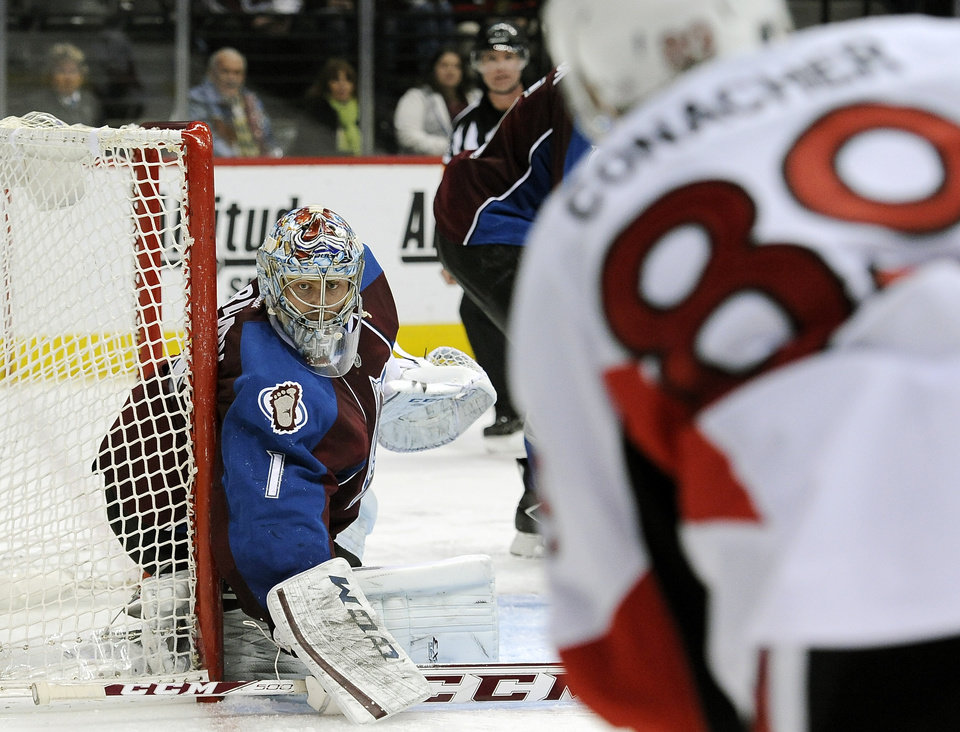 Photo - Colorado Avalanche goalie Semyon Varlamov, left, guards the net in the second period of an NHL hockey game against the Ottawa Senators on Wednesday, Jan. 8, 2014, in Denver. (AP Photo/Chris Schneider)