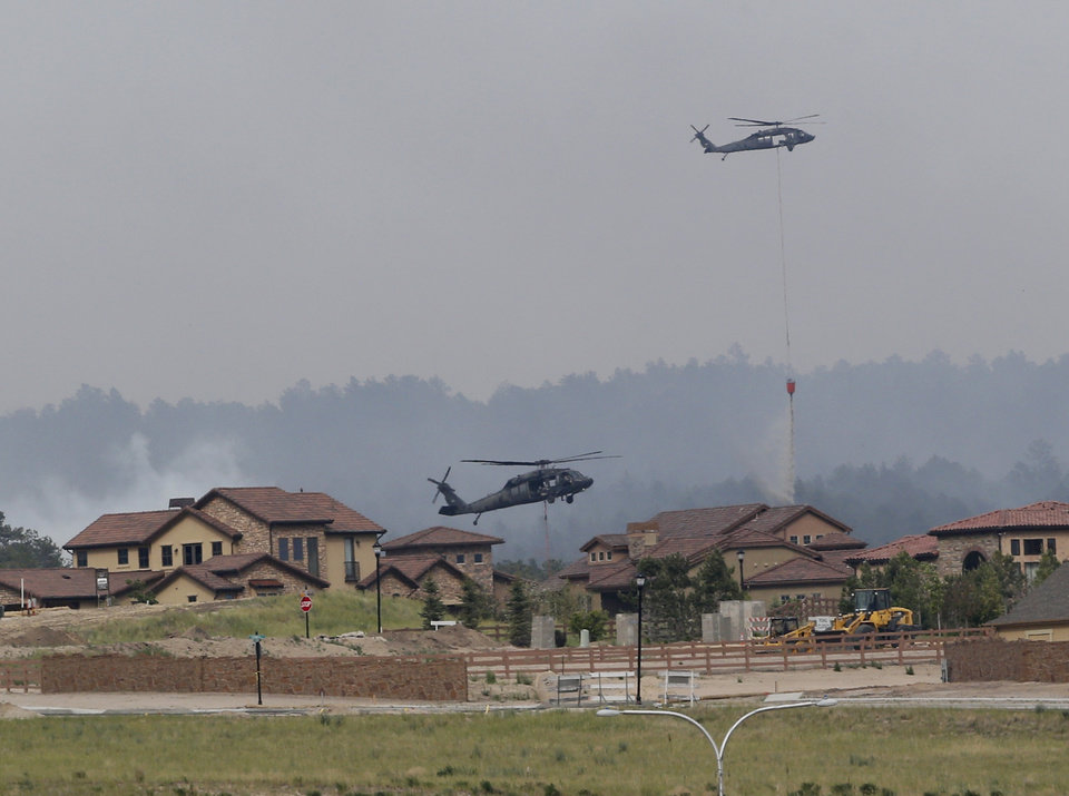 Photo - Army helicopters drop water on the Black Forest wildfire behind houses on the Flying Horse Ranch in Colorado Springs, Colo., on Thursday, June 13, 2013. The residential area was evacuated Thursday. Over 350 homes have been destroyed by the fire since Tuesday. (AP Photo/Ed Andrieski)