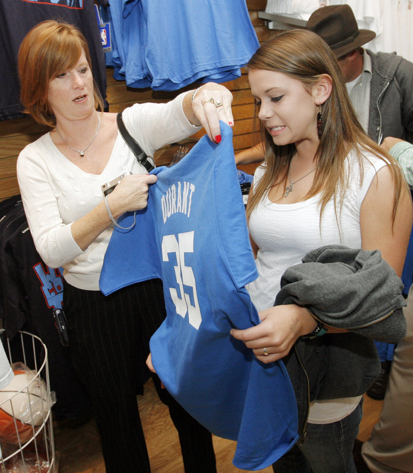 Photo - Donna Powell holds up a shirt over Lauren Powell, 16, inside the OKC Thunder team store after the unveiling of the Oklahoma City Thunder NBA team name at Leadership Square in downtown Oklahoma City, Wednesday, September 3, 2008. NATE BILLINGS, THE OKLAHOMAN