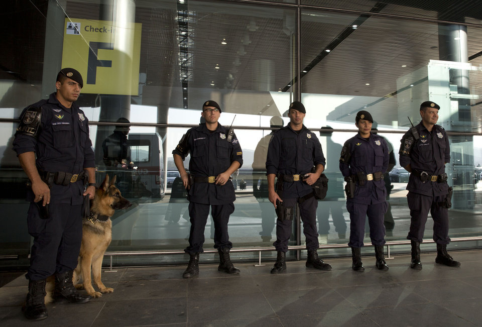 Photo - Policemen stand outside the new terminal 3 at the Sao Paulo International airport in Guarulhos, Brazil, Tuesday, May 20, 2014. The chronic delays in airport renovations have matched those in stadium construction, and officials have acknowledged for a while that visitors will be using unfinished airport facilities. Brazil is trying to assure World Cup tourists that they won't face problems at airports even though not all upgrades will be complete. (AP Photo/Andre Penner)