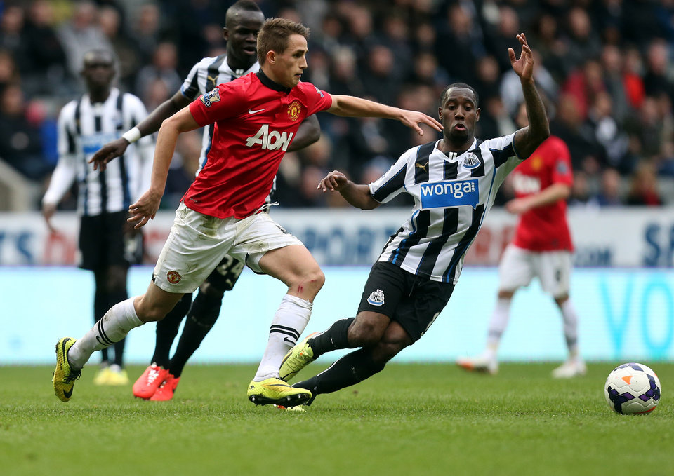 Photo - Manchester United's Adnan Januzaj, left, vies for the ball with Newcastle United's Vurnon Anita, right, during their English Premier League soccer match at St James' Park, Newcastle, England, Saturday, April 5, 2014. (AP Photo/Scott Heppell)