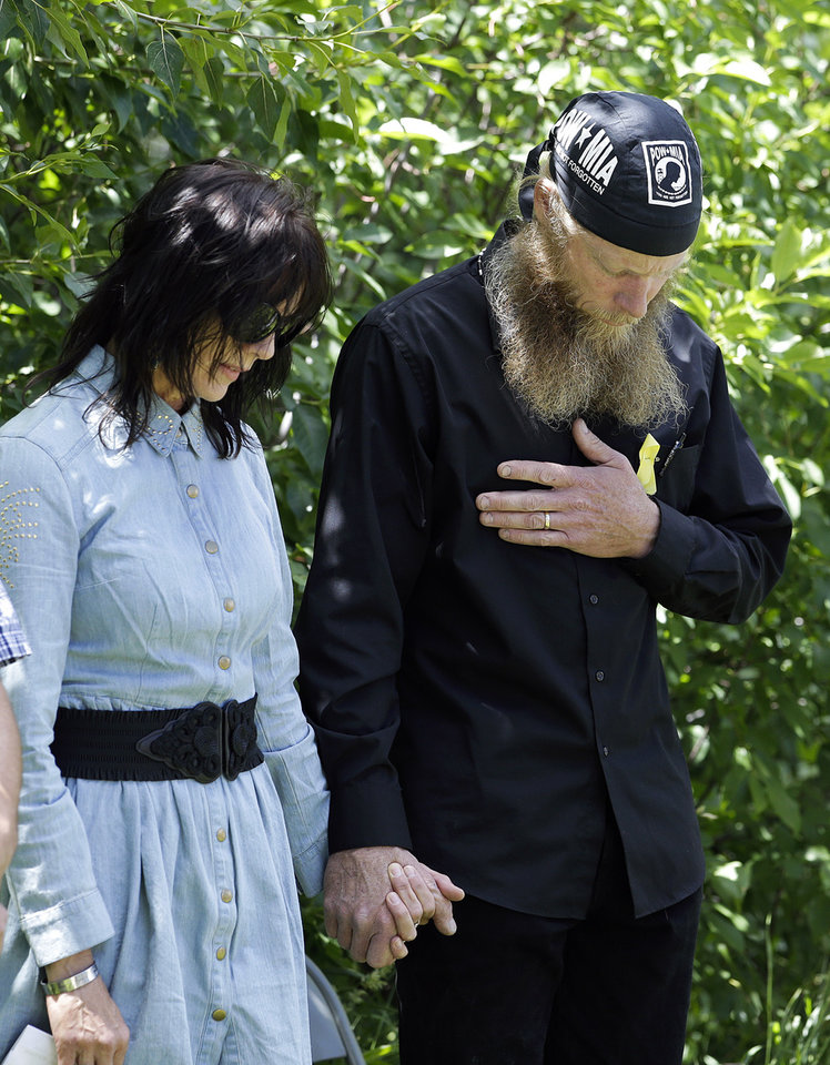 Photo - FILE - In this Saturday, June 22, 2013 file photo, Bob Bergdahl, right, and Jani Bergdahl, the parents of captive U.S. Army Sgt. Bowe Bergdahl, hold hands as they pray at the