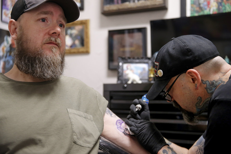 Photo - Joe Salois tattoos Ken Raymond in Oklahoma City, Tuesday, June 25, 2019. [Bryan Terry/The Oklahoman]