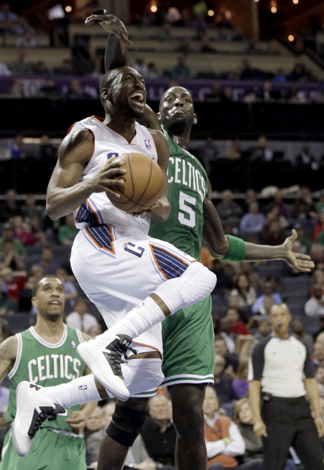 Charlotte Bobcats' Kemba Walker, front, drives past Boston Celtics' Kevin Garnett, rear, during the first half of an NBA basketball game in Charlotte, N.C., Monday, Feb. 11, 2013. (AP Photo/Chuck Burton)