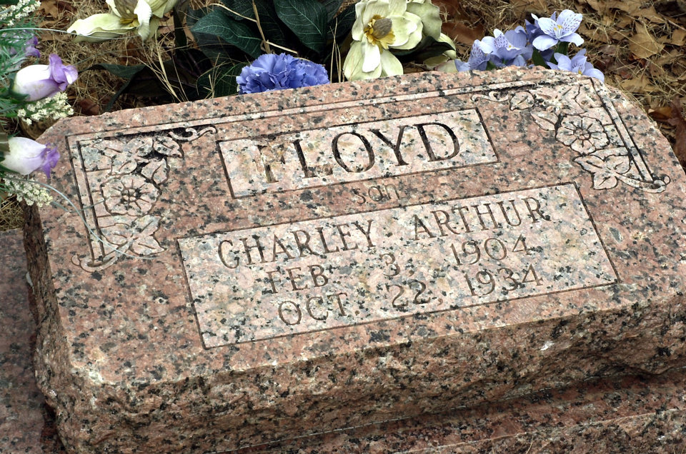 "Photo - ** ADVANCE FOR SUNDAY, FEB. 1 ** The headstone on the grave of Charles ""Pretty Boy"" Floyd rests in the Akins Cemetery in Akins, Okla., Friday, Jan. 30, 2004. On the centennial of Floyd's birth, the notorious bank robber and killer is still remembered as a Robin Hood in his home states of Oklahoma and Arkansas. According to Lloyd's nephew, Jim Lessley of Sallisaw, Okla., Lloyd's headstone was recently replaced because souvenir hunters had chipped away so much of the original marker. (AP Photo/April L. Brown)"