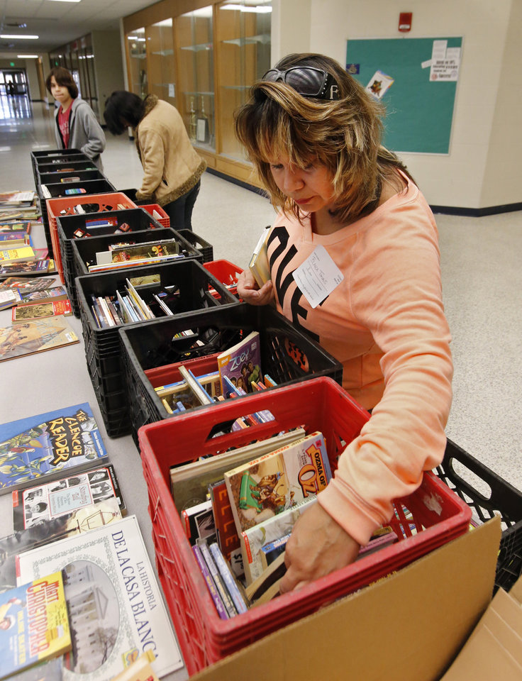 Western Heights Middle School parent Blanca Tovias looks through free books as her child's school kicks off its first day of training for its One Kid Challenge program on Saturday, Dec. 15, 2012, in Oklahoma City, Okla.  Photo by Steve Sisney, The Oklahoman
