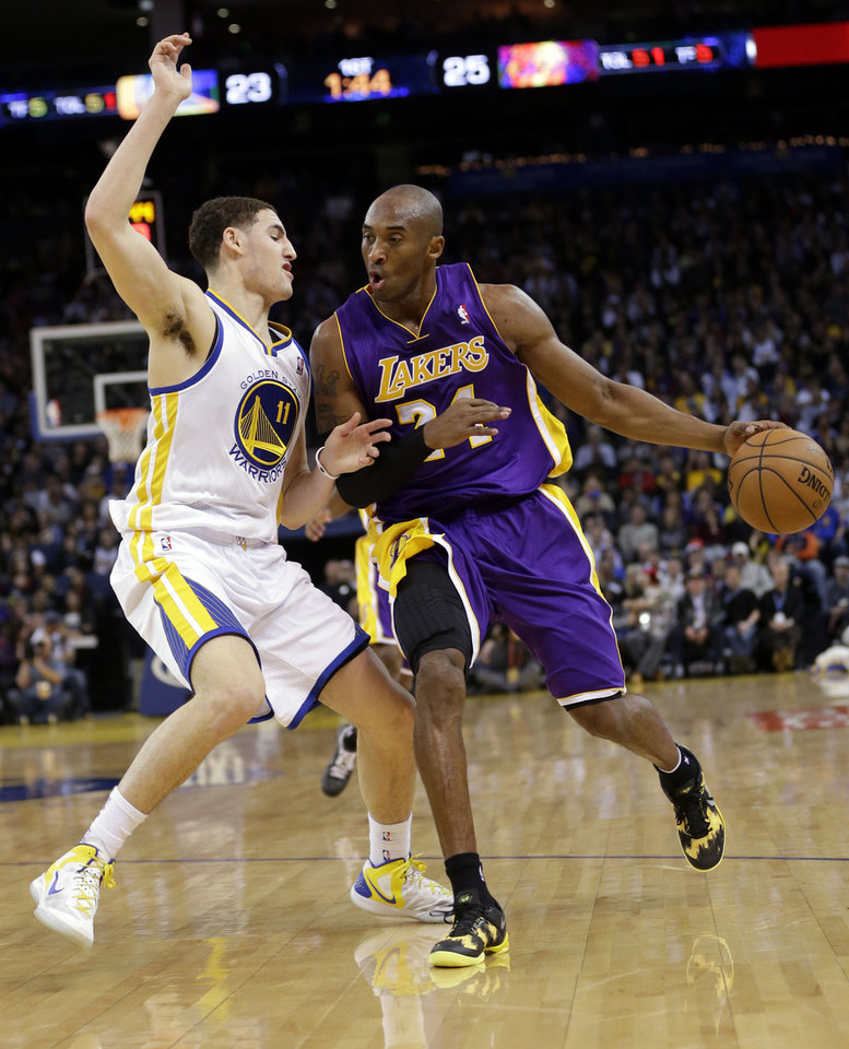 Los Angeles Lakers\' Kobe Bryant (24) dribbles next to Golden State Warriors\' Klay Thompson (11) during the first half of an NBA basketball game in Oakland, Calif., Saturday, Dec. 22, 2012. (AP Photo/Marcio Jose Sanchez)