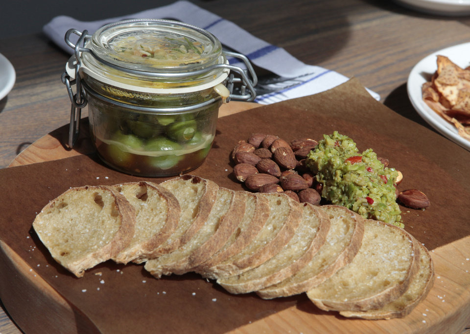 Photo - The warm olives appetizer includes Castelvetrano olives, lemon and rosemary with fresh bread, almonds and tapenade.  David McDaniel - The Oklahoman