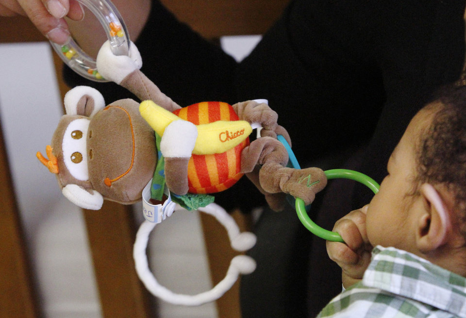 Photo - Above: A baby grasps a toy at a state-run shelter for abused and neglected children in Oklahoma City.