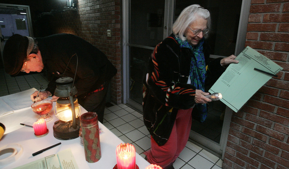 Photo - WINTER WEATHER / ICE STORM 2007 / POWER OUTAGES / ELECTION / VOTING / VOTERS: R to L  - Maureen Bynum heads off to vote with her flashlight as her husband Chet Bynum of Norman signs in by candlelight at Precinct 19 in Berry Road Baptist Church Tuesday, Dec. 11, 2007 in Norman,OK. BY JACONNA AGUIRRE/THE OKLAHOMAN. ORG XMIT: kOD