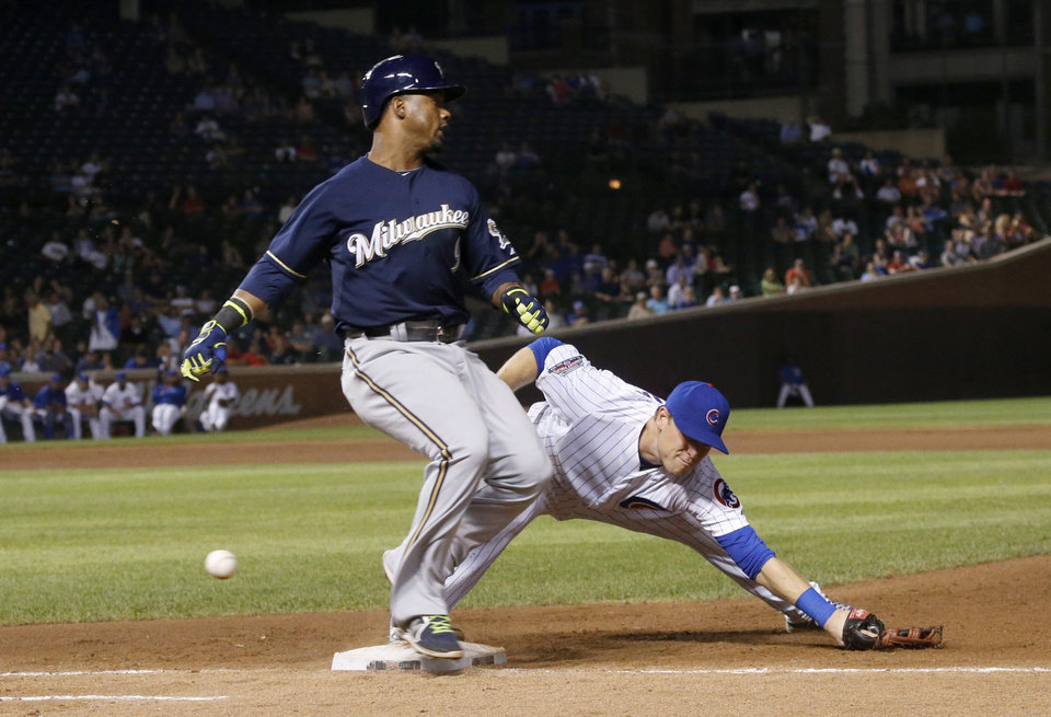 Photo - Milwaukee Brewers' Jean Segura, left, reaches first on a throwing error by Chicago Cubs second baseman Logan Watkins to first baseman Chris Valaika, during the ninth inning of a baseball game Wednesday, Sept. 3, 2014, in Chicago. The Cubs won 6-2. (AP Photo/Charles Rex Arbogast)