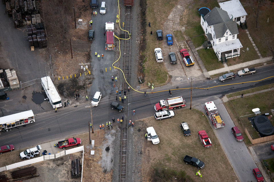 Photo - Emergency personnel respond to an intersection close to where a  freight train derailed in Paulsboro, N.J., Friday, Nov. 30, 2012. People in three southern New Jersey towns were told Friday to stay inside after the freight train derailed and several tanker cars carrying hazardous materials toppled from a bridge and into a creek. (AP Photo/Cliff Owen)