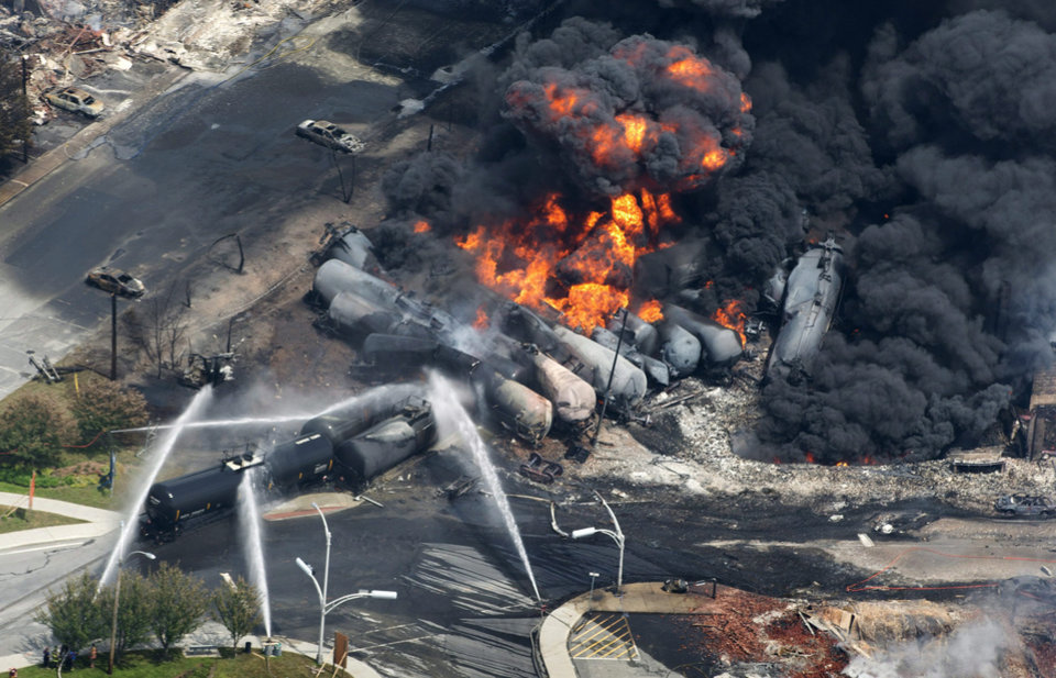 Photo -  In this July 6, 2013, photo, smoke rises from railway cars carrying crude oil after derailing in downtown Lac Megantic, Quebec. AP Photo/The Canadian Press, Paul Chiasson   Paul Chiasson