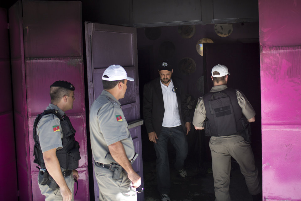 Police enter the Kiss nightclub the day after a fatal fire in Santa Maria, Brazil, Monday, Jan. 28, 2013. A fast-moving fire roared through the crowded, windowless Kiss nightclub in this southern Brazilian city early Sunday, killing more than 230 people. Many of the victims were under 20 years old, including some minors. (AP Photo/Felipe Dana) ORG XMIT: XFD114