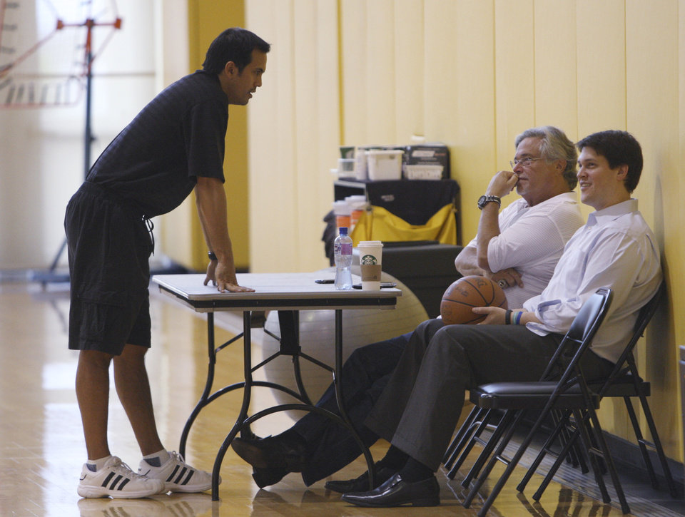Miami Heat coach Erik Spoelstra, left, talks with managing general partner Micky Arison, center, and his son, chief executive officer Nick Arison, as they watch practice Saturday, May 12, 2012, in Miami. The Heat face the Indiana Pacers in the opening game of an NBA basketball Eastern Conference semifinal on Sunday in Miami. (AP Photo/Wilfredo Lee)