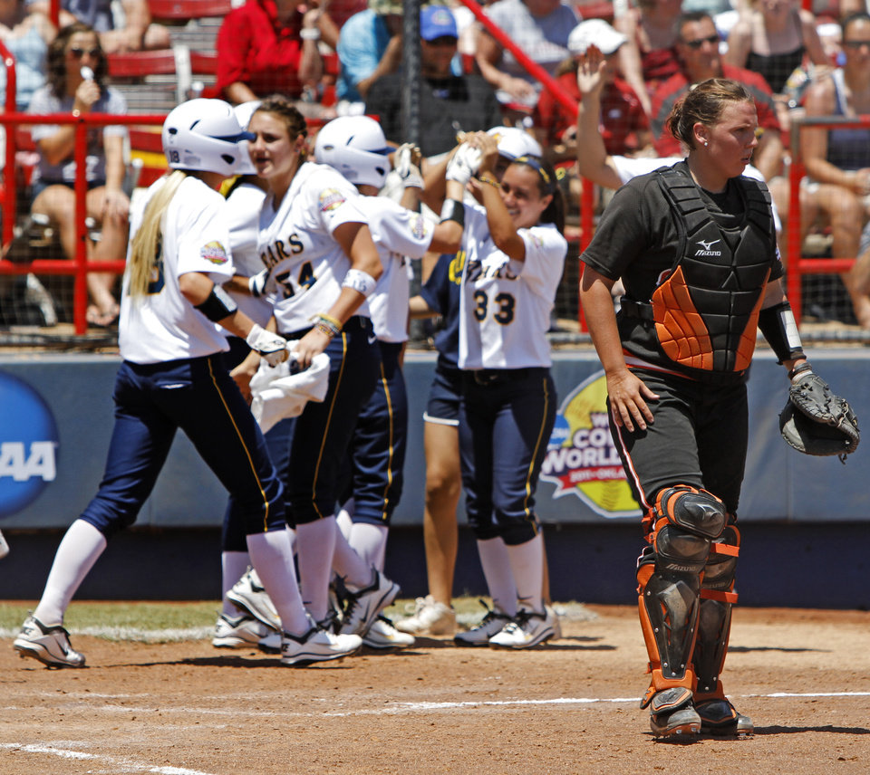 Photo - Oklahoma State's Ashley Boyd (25) walks back for her mask as California celebrates scoring in the fifth inning of a Women's College World Series softball game between Oklahoma State University and California at ASA Hall of Fame Stadium in Oklahoma City, Saturday, June 4, 2011. California won, 6-2. Photo by Bryan Terry, The Oklahoman