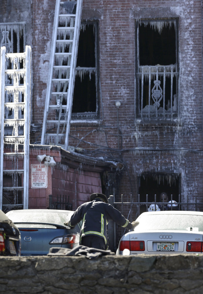 Photo - A firefighter pauses between cars near the burned remains of a four-story brownstone, Thursday, March 27, 2014, in Boston. Two firefighters, Lt. Edward Walsh and Michael Kennedy, lost their lives fighting a nine-alarm blaze that destroyed the structure in Boston's Back Bay neighborhood Wednesday, March 26, 2014. (AP Photo/Steven Senne)
