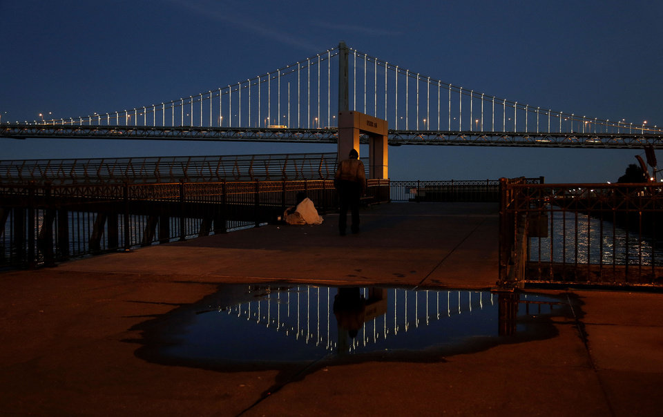 Photo - In this Wednesday, Feb. 20, 2013,  photo, lights  are reflected on the San Francisco-Oakland Bay Bridge on Pier 14 in San Francisco. The San Francisco-Oakland Bay Bridge has been turned into the latest, and by far the biggest, backdrop for New York artist Leo Villareal, who has individually programmed 25,000 white lights spaced a foot apart on 300 of the span's vertical cables to create what is being billed as the world's largest illuminated sculpture. (AP Photo/Jeff Chiu)