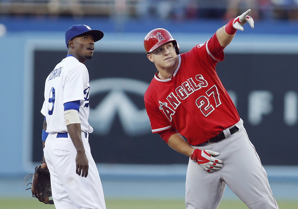 Photo - Los Angeles Angels' Mike Trout, right, points something out to Los Angeles Dodgers second baseman Dee Gordon, left, after hitting a double to score Kole Calhoun during the first inning of a baseball game, Monday, August 4, 2014, in Los Angeles. (AP Photo/Danny Moloshok)