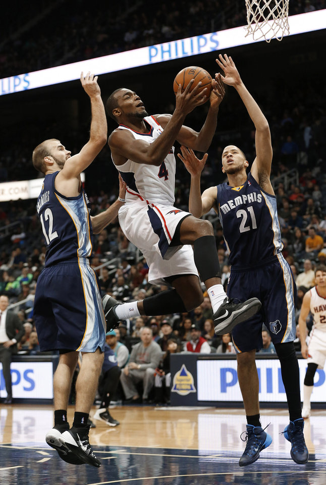 Photo - Atlanta Hawks forward Paul Millsap (4) is fouled as he drives between Memphis Grizzlies' Nick Calathes (12) and  Tayshaun Prince (21) during the first half of an NBA basketball game Saturday, Feb. 8, 2014, in Atlanta. (AP Photo/John Bazemore)